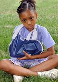 pic of triage  - Girl sitting on the lawn looking sad because her arm is in a sling 