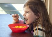 Young Girl Eating Macaroni And Cheese