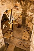 stock photo of torture  - Holding cell in a medieval prison with torture instruments - JPG