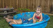 Young Boy Looking Out Of His Paddling Pool,young Girl Smiling At The Camera Trying To Sit On A Ball