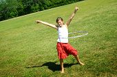 stock photo of hulahoop  - young preteen having fun in a park with hula hoop - JPG