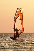 Windsurfer On Waves Of A Gulf On A Sunset
