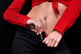 stock photo of pierced belly button  - Nice and sexy navel piercing on a girl dressed in red - JPG