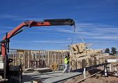 Workman guides trusses onto new houses under construction