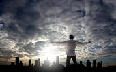 stock photo of city silhouette  - man with open arms facing a city - JPG