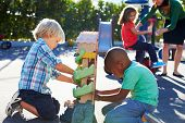 stock photo of playground school  - Two Boys Playing With Toy In Playground - JPG