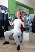 The young sporting woman in fitness center trains