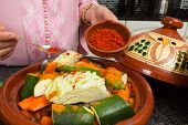 Traditional Moroccan immigrant woman in Europe adding spices to her tajine during Ramadan in her mod