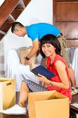 Real estate market - Young Indonesian couple moving in a home or apartment, they unpacking moving bo