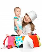 Mom And Baby Girl With Suitcase And Clothes Ready For Traveling On Vacation