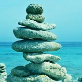 picture of a typical stack of balanced stones in Cap de Cavalleria, Menorca, Balearic Islands, Spain, with a retro effect