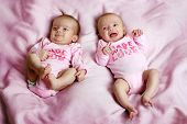 image of twin baby girls  - Some cute fraternal twins on a pink blanket - JPG
