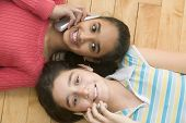 Portrait of two girls laying on floor talking on cell phones