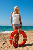 stock photo of lifeline  - Beautiful slim girl on the beach with a lifeline