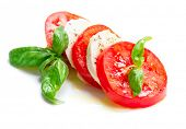 Caprese Salad. Tomato and Mozzarella slices with basil leaves. Isolated on white background