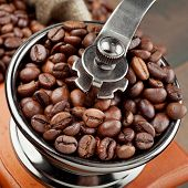 picture of wooden box from coffee mill  - coffee grinder with coffee beans on kitchen table