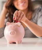 stock photo of insert  - Woman Putting Coin In Piggy Bank - JPG