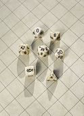 image of dd  - Polyhedral dice on a blank one inch square grid game map used in roleplaying game - JPG