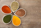 stock photo of flax seed  - Colourful dried or ground herbs and spices in petal shaped bowls - JPG