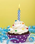 stock photo of icing  - A birthday cup cake with vanilla icing - JPG