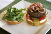 Hamburger On Plate With Onions On Top