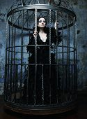 Fashion model in fantasy dress posing in steel cage.