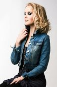 portrait of a young beautiful woman with loose curly hair blond hair wearing blue jean jacket with r