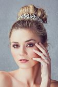 Portrait of a beautiful blond bride with a diamante headpiece. Hair in romantic top knot bun hairsty