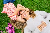 Beautiful mother and daughter lying together outside on grass, Happy intimate moment, Cute little gi