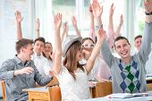 Smiling highschool students in classroom holding hands in the air