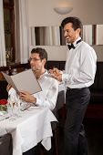 Waiter Serving A Couple In A Restaurant