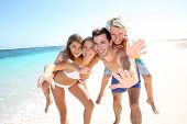 pic of piggyback ride  - Parents giving piggyback ride to kids at the beach - JPG