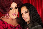 foto of transvestite  - Big transvestite with sensual Hispanic man in front of curtain - JPG