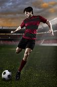 picture of negro  - Soccer player in a red and black uniform kicking on a stadium - JPG