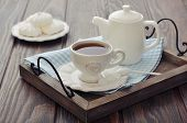 stock photo of trays  - Cup of tea and teapot on wooden tray closeup - JPG