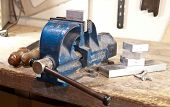 stock photo of workbench  - Vice with a block of metal on a wooden workbench - JPG