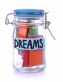 Dreams written on color paper in glass jar, isolated on white