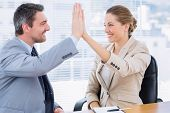 picture of half-dressed  - Smartly dressed young man and woman giving high five in a business meeting at office desk - JPG