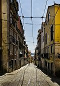 View of an old street with copperstones, rails and colorful houses in Lisbon, Portugal