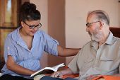 companion or grandchild reading to elderly senior or grandfather