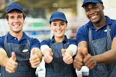 group of happy supermarket workers thumbs up