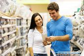 cheerful young couple shopping in hardware store