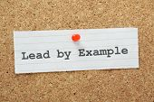 picture of character traits  - The phrase Lead By Example typed on a paper note and pinned to a cork notice board - JPG