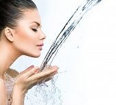 Beautiful Model Girl with splashes of water in her hands. Beautiful Smiling Woman under splash of wa