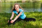 foto of hamstring  - Exercise woman stretching hamstring leg muscles during outdoor running workout - JPG
