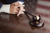 Male Judge Rests Folded Hands Behind Gavel with American Flag Reflection on Wooden Table.