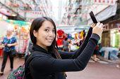 Woman take selfie in Hong Kong temple street