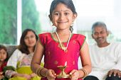 Indian family celebrate diwali or deepavali at home, little girl with traditional clothing sari, han