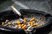 picture of butts  - A cigarette with ash end rests on the side of a nearly full and dirty ashtray containing much ash and many crushed cigarette butts - JPG