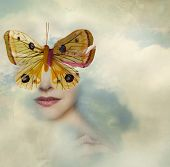 stock photo of surrealism  - Surreal image representing a female portrait shrouded in the clouds with a butterfly instead of her eyes - JPG